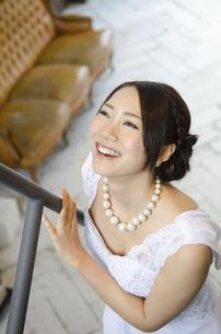 手すりを触りながら笑うドレス姿の女性の写真素材 [FYI01704812]