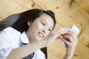 床に寝転がって携帯電話を見ている制服姿の女性の写真素材 [FYI01704852]