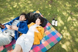 ピクニックマットの上に寝転がる男女の写真素材 [FYI01704883]