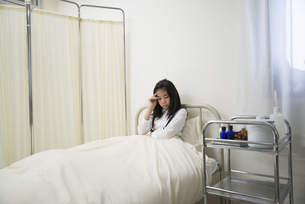 保健室のベッドにいる具合の悪そうな小学生の女の子の写真素材 [FYI01704904]