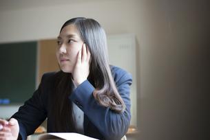 机に座って話を聞いている女子高校生の写真素材 [FYI01704912]