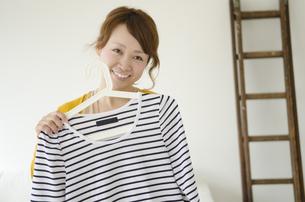 ハンガーに掛かった服を当てる笑顔の女性の写真素材 [FYI01704930]