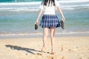 両手に靴を持って波打ち際に向かう制服姿の女の子の写真素材 [FYI01704954]