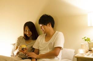 ベッドで目覚まし時計をセットするカップルの写真素材 [FYI01704958]
