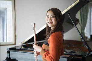 ピアノの前でフルートを持っている女性の写真素材 [FYI01704978]