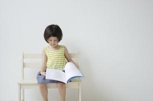ベンチに座って絵本をめくる女の子の写真素材 [FYI01704984]