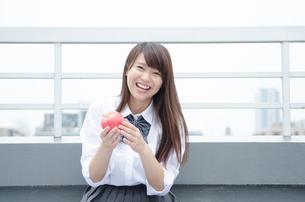 りんごを持つ笑顔の制服姿の女性の写真素材 [FYI01704992]