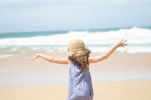 ビーチで両手を広げている女の子の後ろ姿の写真素材 [FYI01705004]