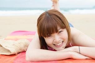 ビーチに寝そべって笑うビキニ姿の女性の写真素材 [FYI01705008]