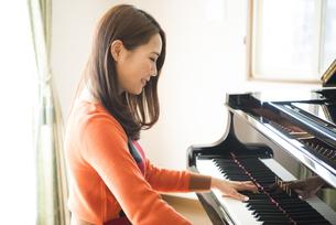 部屋でピアノを弾いている女性の写真素材 [FYI01705087]