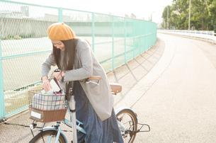 自転車の荷物を触っている女性の写真素材 [FYI01705124]