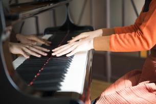 部屋でピアノを弾いている女性の写真素材 [FYI01705128]