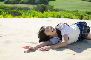 砂浜に笑いながら転がる制服姿の女の子の写真素材 [FYI01705136]