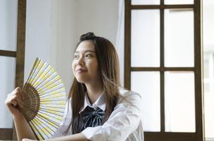 扇子をあおいでいる制服姿の女性の写真素材 [FYI01705139]