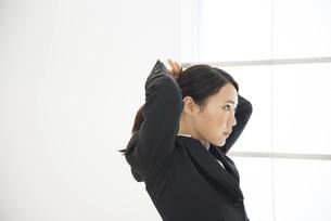 髪を結んでいるスーツ姿の女性の写真素材 [FYI01705150]