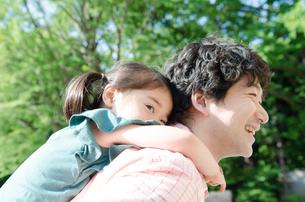 笑顔のお父さんにおんぶされる女の子の写真素材 [FYI01705161]