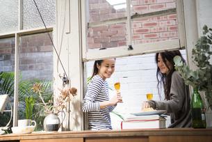 家で飲みながらおしゃべりをしている女性2人の写真素材 [FYI01705184]