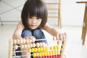 100玉そろばんで遊んでいる女の子の写真素材 [FYI01705190]