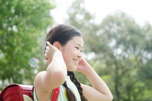 ランドセルを背負って耳に手を当てる女の子の写真素材 [FYI01705195]