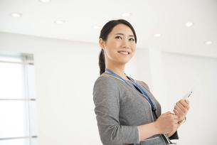 タブレットを抱えて笑っている女性の写真素材 [FYI01705199]