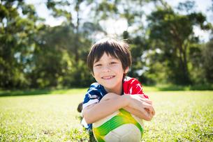 サッカーボールと一緒に寝そべっている男の子の写真素材 [FYI01705227]