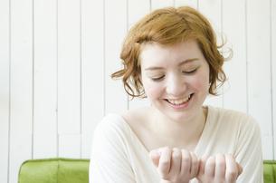 室内で自分の爪を見ているハーフの女性の写真素材 [FYI01705238]