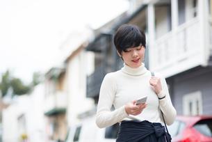 街でスマホを見ている女性の写真素材 [FYI01705244]