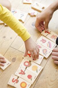 英語のパズルで遊ぶ親子の手の写真素材 [FYI01705246]