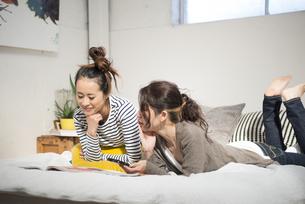 ベッドの上で話している女性2人の写真素材 [FYI01705254]