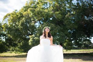 ドレスを広げているウェディングドレス姿の女性の写真素材 [FYI01705256]