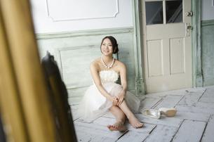 白いドレスを着て床に座る女性の写真素材 [FYI01705298]
