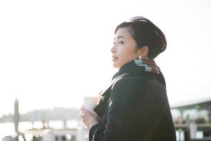 水辺でコーヒーを持って遠くを見ている女性の写真素材 [FYI01705327]