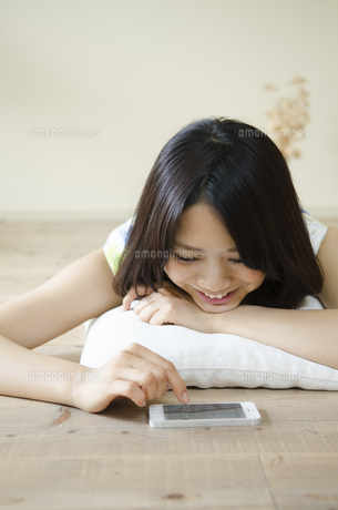 床に寝そべってスマートフォンを操作する女性の写真素材 [FYI01705329]