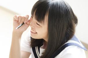 鉛筆を持って笑っている制服姿の女の子の写真素材 [FYI01705333]
