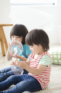 風船を膨らませている男の子と女の子の写真素材 [FYI01705351]