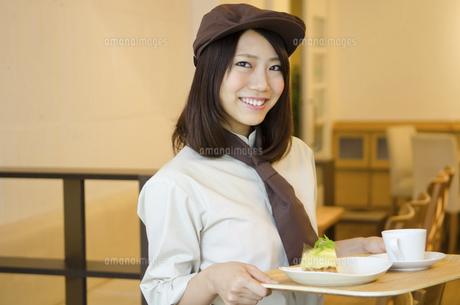 制服を着てカフェで働く女性の写真素材 [FYI01705355]