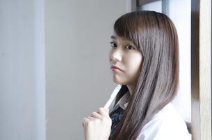 ペンを持って考えている制服姿の女性の写真素材 [FYI01705365]
