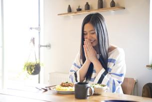 テーブルでご飯を食べようとしている女性の写真素材 [FYI01705373]