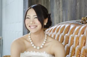 白いドレスを着てソファに座る女性の写真素材 [FYI01705385]