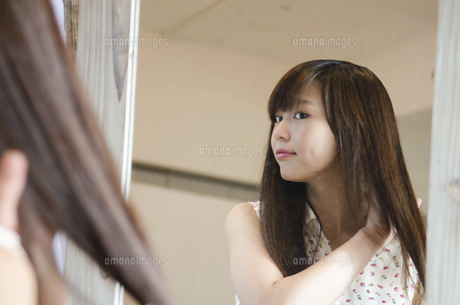 鏡の前で髪をセットする女性の写真素材 [FYI01705391]