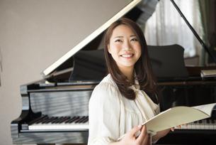 ピアノの前で楽譜を持っている女性の写真素材 [FYI01705394]