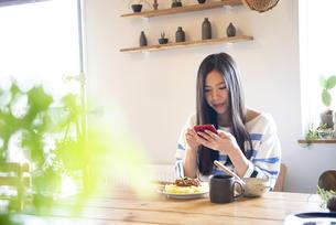 テーブルでスマホを操作している女性の写真素材 [FYI01705411]