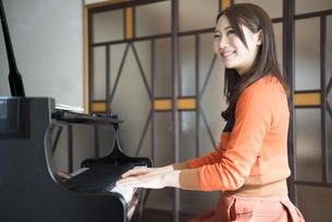 室内でグランドピアノを弾いている女性の写真素材 [FYI01705413]