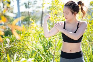 トレーニングウェアで腕の筋肉をチェックしている女性の写真素材 [FYI01705416]
