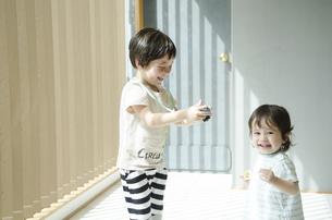 カメラで小さい子を撮影している子供の写真素材 [FYI01705425]