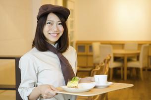 制服を着てカフェで働く女性の写真素材 [FYI01705437]