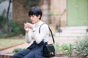 街でコーヒーを飲んでいる女性の写真素材 [FYI01705438]
