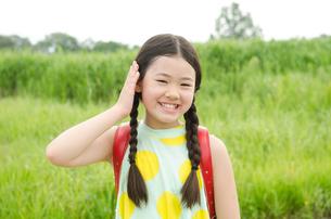ランドセルを背負って耳に手を当てている女の子の写真素材 [FYI01705444]