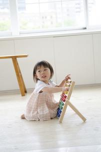 部屋の中で100玉そろばんで遊ぶ女の子の写真素材 [FYI01705446]