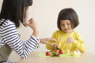 果物を切っている姉妹の写真素材 [FYI01705452]